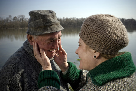 unify: Senior couple by river, woman touching mans face, smiling, close-up