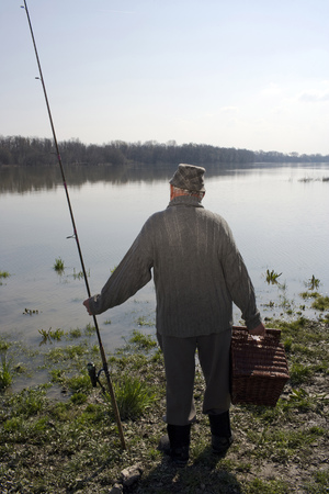 passtime: Senior man standing by river holding fishing rod, rear view