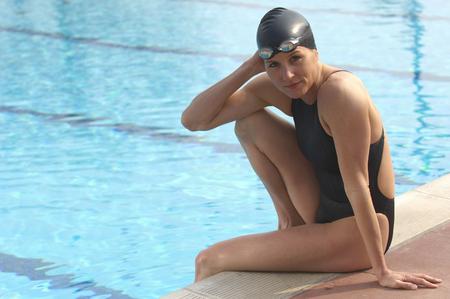 Female swimmer sitting on edge of pool, portrait