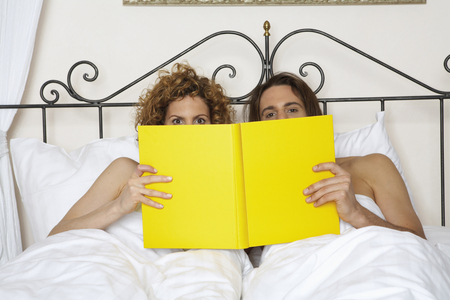 young couple in bed holding yellow book, portrait