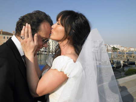 Bride kissing grooms forehead. Grand Canal, Venice, Italy.