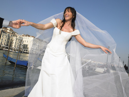 Italy, Venice, bride holding mans hand, smiling