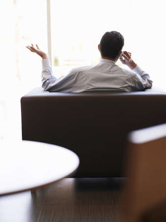 40 something: Businessman sitting in office using mobile phone, rear view LANG_EVOIMAGES