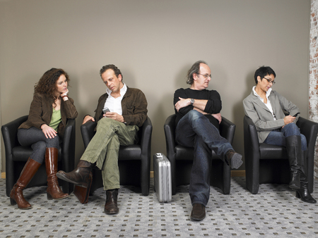 50 something: Two businesswomen and two businessmen sitting in waiting room. Brussels, Belgium.