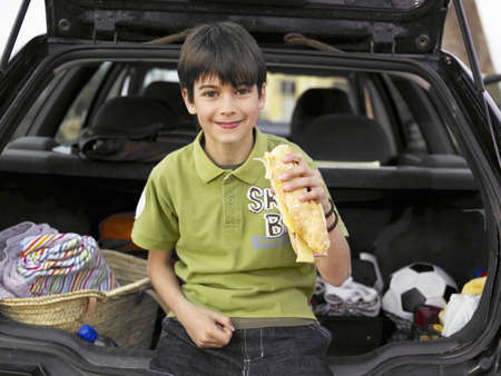 passtime: Boy (8-10) resting against open boot of parked car, eating baguette, portrait