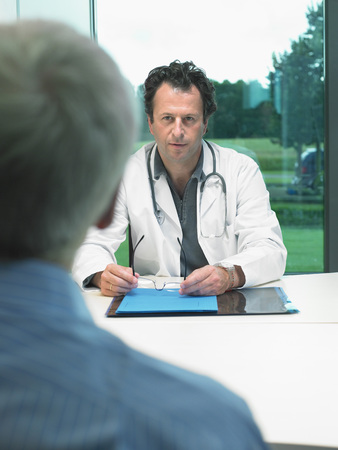 Male doctor at his desk talking with mature male patient. LANG_EVOIMAGES