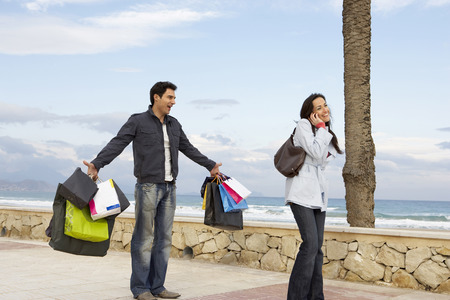 Woman using mobile phone, man holding out shopping bags in background