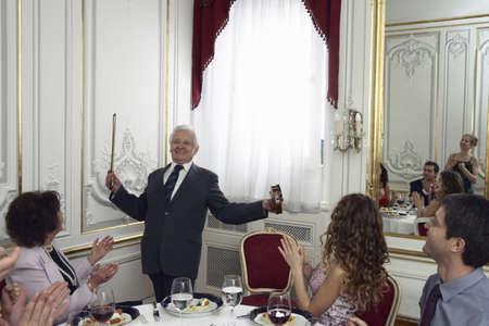 40 something: Multigenerational family applauding senior man with violin, smiling LANG_EVOIMAGES
