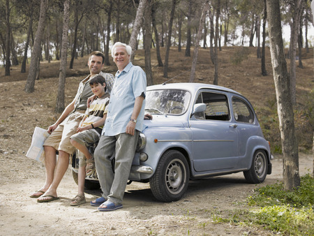50 something: Boy (8-10) leaning on car bonnet with father and grandfather, man holding map