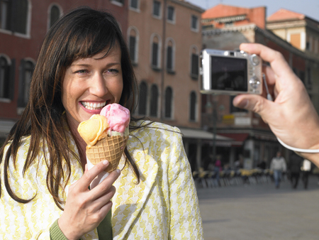 Close up of mans hand taking photo of woman eating ice cream. Venice, Italy. LANG_EVOIMAGES