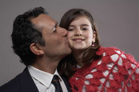 40 something: Father kissing daughter (9-11) on cheek  LANG_EVOIMAGES