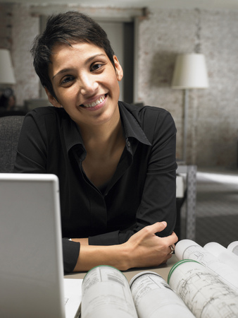 Female architect sitting at desk, smiling, portrait
