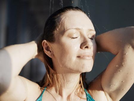 passtime: Woman beneath shower, eyes closed