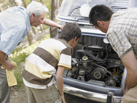 50 something: Boy (8-10) looking at car engine with father and grandfather, rear view LANG_EVOIMAGES