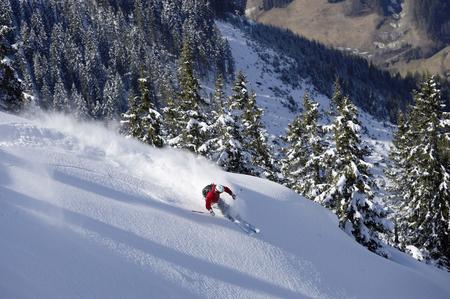 Man skiing down snow mountain slope, overhead view