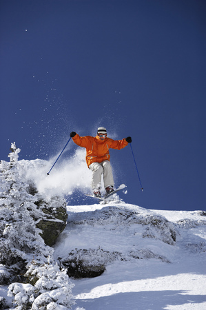 Austria, Saalbach, male skier jumping over mound past trees on slope