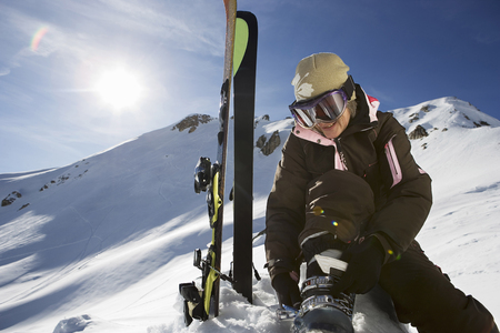 get away: Mature female skier fastening boot bindings on mountain