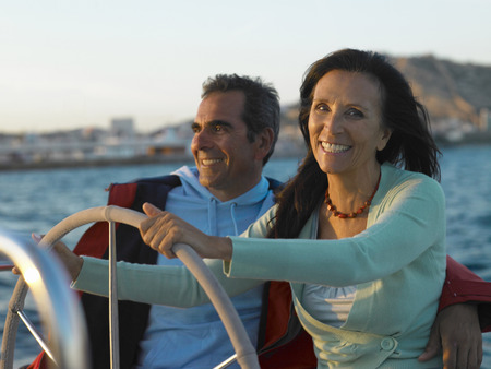 Mature couple at wheel of yacht, smiling LANG_EVOIMAGES