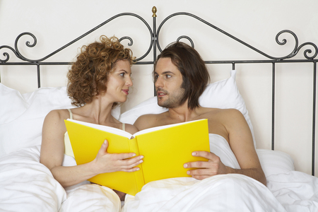 young couple in bed holding yellow book LANG_EVOIMAGES