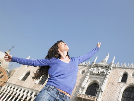 Smiling woman with arms outstretched. Palazzo Ducale, Venice, Italy.