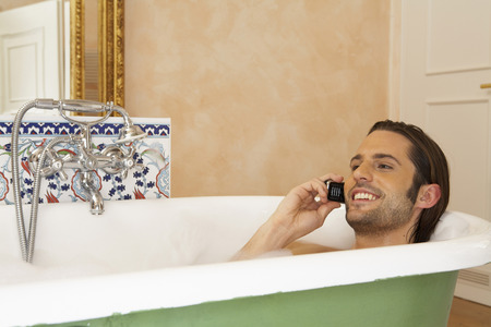 passtime: young man smiling in bath holding mobile phone, high section