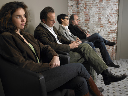50 something: Two businesswomen and two businessmen sitting in waiting room, side view. Brussels, Belgium.