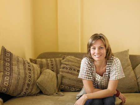 passtime: Woman sitting on sofa at home, smiling, front view, portrait LANG_EVOIMAGES