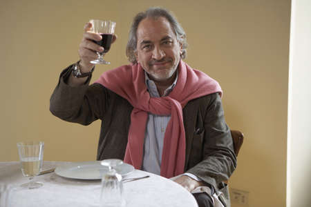 fulfilled: Senior man holding up wine at table, portrait