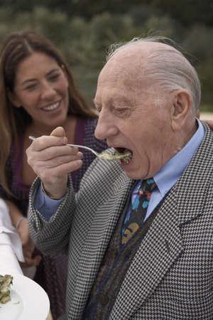 enjoys: Senior man eating at table outdoors