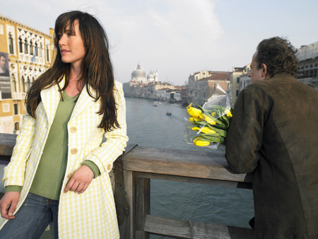 get away: Woman and man with flowers on Academia Bridge overlooking Grand Canal. Venice, Italy.