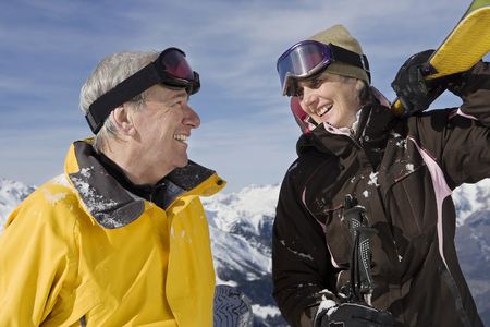 Mature couple in ski-wear holding Skis on mountain