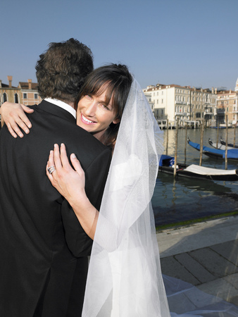thirtysomething: Italy, Venice, bride and groom embracing, woman smiling