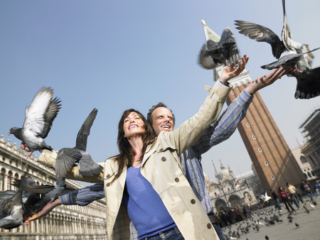 Portrait of couple with pigeons. St Marks Square, Venice, Italy.