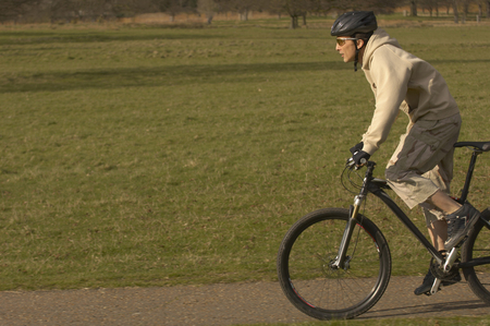 passtime: Man cycling in park LANG_EVOIMAGES