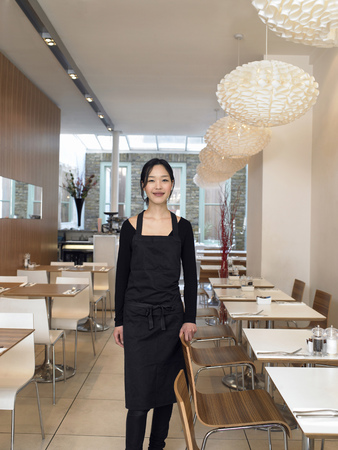 formulate: Young waitress standing in empty restaurant, smiling, portrait