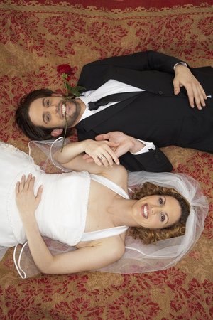 formals: young bridal couple  smiling lying on bed, overhead view, portrait