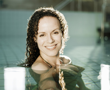 Woman standing in swimming pool, smiling, portrait