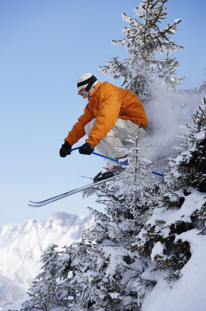 passtime: Austria, Saalbach, male skier jumping through trees on slope LANG_EVOIMAGES