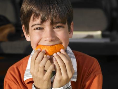 Boy (8-10) eating orange, close-up, portrait LANG_EVOIMAGES