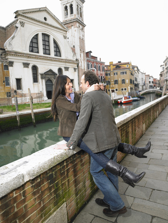 30 to 40 year olds: Couple embracing on parapet. Dorsoduro, Venice, Italy.