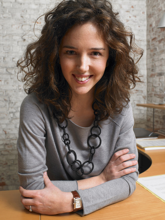 appearance: Woman sitting at desk smiling at camera. ,Brussels, Belgium. LANG_EVOIMAGES