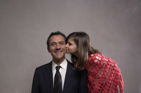 40 something: Daughter (9-11) kissing smiling father on cheek  LANG_EVOIMAGES