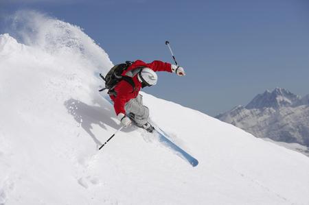 Austria, Saalbach, man skiing down mountain slope