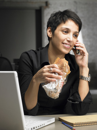 differential: Businesswoman talking on the phone while having snack. Brussels, Belgium. LANG_EVOIMAGES