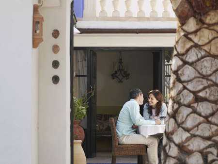 passtime: Couple sitting on garden terrace about to kiss