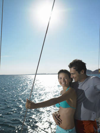 freeing: Young couple standing on yacht at sea, smiling LANG_EVOIMAGES