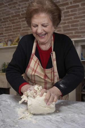 passtime: Senior woman kneading dough, smiling