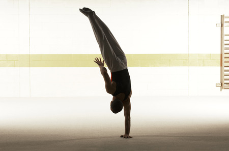 Male gymnast balancing on one hand on floor, rear view