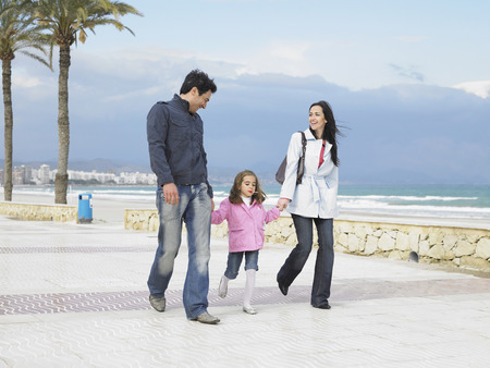 Mother and father walking along palm lined pavement by the sea with young daughter (6-8). Alicante, Spain. LANG_EVOIMAGES