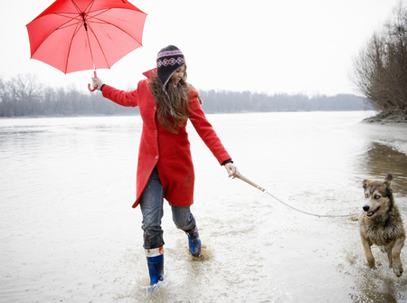 Young woman holding umbrella, running in river with dog, smiling LANG_EVOIMAGES